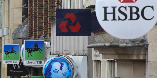 Signs sit outside branches of a Lloyds TSB bank, part of the Lloyds Banking Group Plc, a Barclays Plc bank, a NatWest bank, part of the Royal Bank of Scotland Group Plc (RBS), and a HSBC Holdings Plc bank in Staines, U.K., on Tuesday, Dec. 18, 2012. The European Union is leading a probe into Libor rigging that could see global banks fined as much as 10 percent of their annual revenue. Photographer: Chris Ratcliffe/Bloomberg via Getty Images
