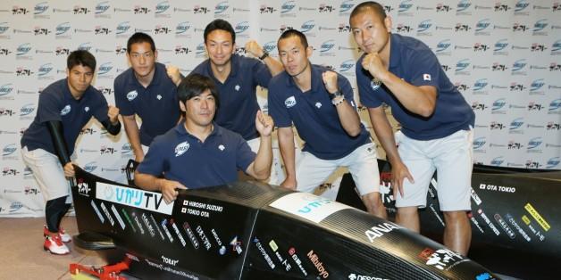 完成したそり「下町ボブスレー2号機」が披露され、ポーズを取る鈴木寛(左から3人目手前)ら=2013年10月8日、東京都大田区