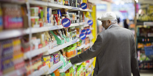 A customer looks at the price of an item displayed for sale on a shelf inside a Tesco Metro store