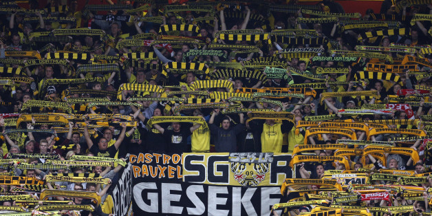 Borussia Dortmund's fans hold up scarves before the UEFA Champions League Group F football match between Arsenal and Borussia Dortmund at the Emirates Stadium, north London, on October 22, 2013. AFP PHOTO/ADRIAN DENNIS        (Photo credit should read ADRIAN DENNIS/AFP/Getty Images)