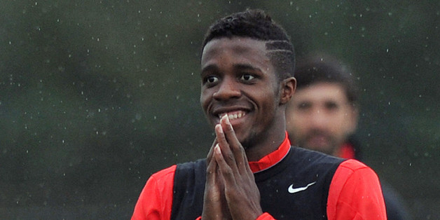 Manchester United's Ivorian-born English striker Wilfried Zaha smiles as he takes part in a training session in Manchester, Northwest England, on October 22, 2014, ahead of the team's  Champions League group A football match against Real Sociedad on October 23. AFP PHOTO/PAUL ELLIS        (Photo credit should read PAUL ELLIS/AFP/Getty Images)