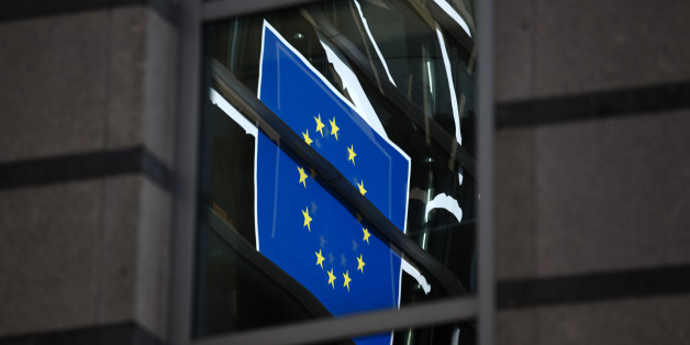 The flag of the European Union (EU) reflects off windows at the parliament building in Brussels, Belgium, on Thursday, Sept. 26, 2013. The U.K. challenged European Union caps on banker bonuses at the bloc's highest court, marking its third court battle against the EU as the region overhauls its financial rules. Photographer: Jasper Juinen/Bloomberg via Getty Images