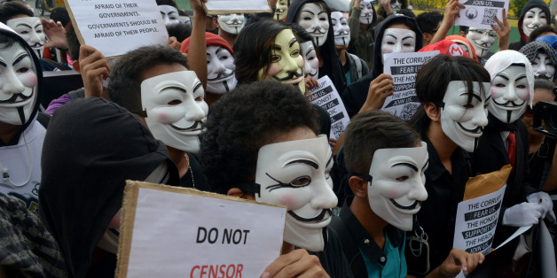 Protesters wearing Guy Fawkes masks display placards during a rally outside the House of Representatives in suburban Quezon city, north of Manila on November 5, 2013. Some 100 masked members of the hacking group Anonymous Philippines marched on parliament on November 5, denouncing corruption and pledging more cyber attacks, a week after 30 government websites were paralysed.    AFP PHOTO / Jay DIRECTO        (Photo credit should read JAY DIRECTO/AFP/Getty Images)