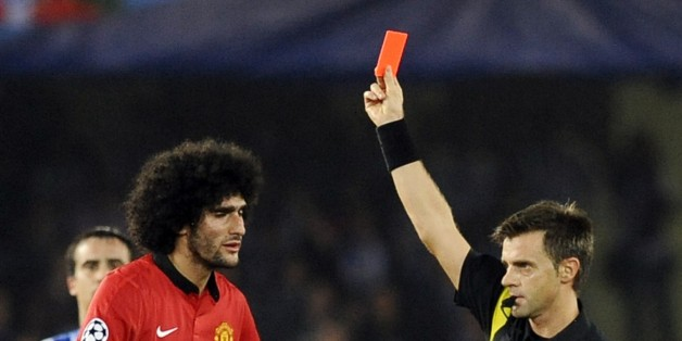 Manchester United's Belgian midfielder Marouane Fellaini (L) receives a red card during the UEFA Champions League Group football match Real Sociedad vs Manchester United at the Anoeta stadium in San Sebastian on November 5, 2013. Match ended 0-0 in a draw. AFP PHOTO / RAFA RIVAS        (Photo credit should read RAFA RIVAS/AFP/Getty Images)