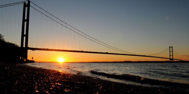 The sun rises behind the Humber Bridge near Hull, East Yorkshire.