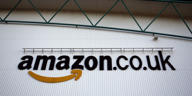 A logo sits on a wall outside the Amazon.co.uk Marston Gate 'Fulfillment Center,' the U.K. site of Amazon.com Inc. in Ridgmont, U.K., on Monday, Dec. 3, 2012. U.K. consumer confidence unexpectedly increased to an 18-month high in November as Britons become more optimistic about the economy and their finances, GfK NOP Ltd. said. Photographer: Simon Dawson/Bloomberg via Getty Images