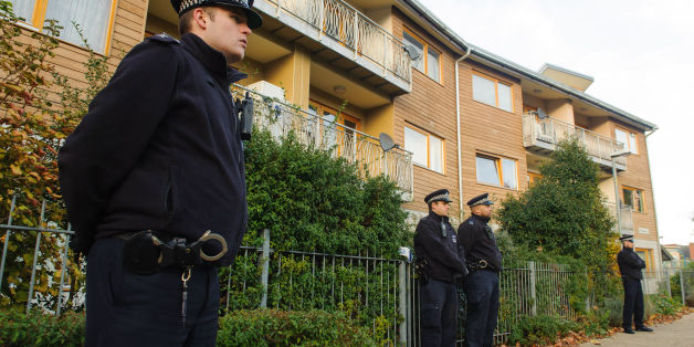 Police officers stand outside flats in Brixton, south London, as police are conducting house-to-house inquires in the area where three women were allegedly held as slaves for at least 30 years were rescued.