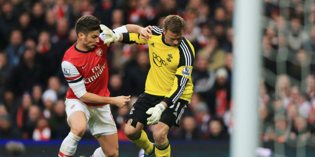 Arsenal's Olivier Giroud (left) challeges Southampton's Artur Boruc to then go on and score during the Barclays Premier League match at Emirates Stadium, London.
