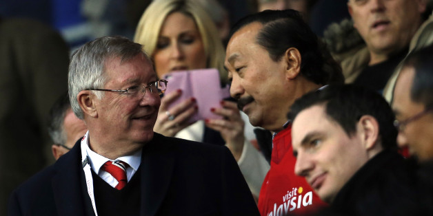 Manchester United's Scottish former manager Alex Ferguson (L) stands with Cardiff City's Malaysian majority shareholder Vincent Tan (R) ahead of the English Premier League football match between Cardiff City and Manchester United at Cardiff City Stadium in Cardiff, south Wales on November 24, 2013. AFP PHOTO/ADRIAN DENNIS RESTRICTED TO EDITORIAL USE. No use with unauthorized audio, video, data, fixture lists, club/league logos or live services. Online in-match use limited to 45 images, no video
