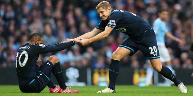 MANCHESTER, ENGLAND - NOVEMBER 24:  Michael Dawson of Tottenham Hotspur helps Sandro to his feet during the Barclays Premier League match between Manchester City and Tottenham Hotspur at Etihad Stadium on November 24, 2013 in Manchester, England.  (Photo by Alex Livesey/Getty Images)