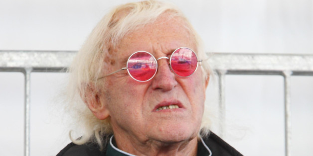 Sir Jimmy Savile watches as Britain's Queen Elizabeth II names Cunard's newest cruise ship, the Queen Elizabeth in Southampton.