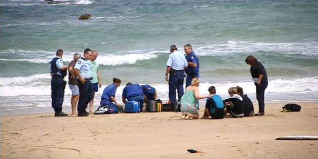 Paramedics assist the teenager after the shark attack