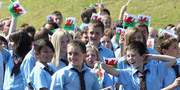 Children wave Welsh Flags as Prince Charles, Prince of Wales, makes a speech during a visit to Treorchy Comprehensive School. in Wales.