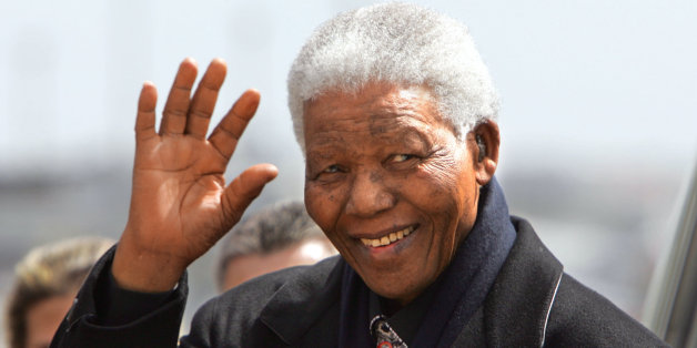 Former South African President Nelson Mandela salutes upon his arrival at Madrid's Barajas airport 21 May 2004 to attend the wedding of Spanish Crown Prince Felipe of Bourbon and former TVE journalist Letizia Ortiz.  AFP PHOTO Javier SORIANO (Photo credit should read JAVIER SORIANO/AFP/Getty Images)