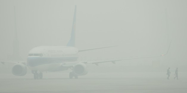 An aircraft is barely visible through thick smog on the tarmac of Hongqiao airport in Shanghai as severe pollution blankets the city on December 6, 2013. The cities most harmful PM2.5 density soared to 468 micrograms per cubic metre by midnight more than 10 times the level deemed safe by the World Health Organization state media said. AFP PHOTO/Peter PARKS        (Photo credit should read PETER PARKS/AFP/Getty Images)