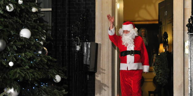 A man dressed as Father Christmas waves as he leaves the annual Downing Street children's christmas Party at 10 Downing Street in central London on December 17, 2012. AFP PHOTO / CARL COURT        (Photo credit should read CARL COURT/AFP/Getty Images)