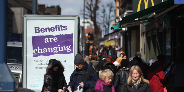 LONDON, ENGLAND - APRIL 02:  Members of the public in North London walk past a poster informing of changes to the benefits and tax system that have come into force yesterday, on April 2, 2013 in London, England. The widespread changes include a cut in housing benefit payments for working-age social housing tenants whose property is deemed larger than they need and council tax support payments being administered locally.  (Photo by Oli Scarff/Getty Images)