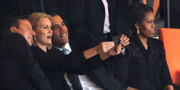 President  Barack Obama (R) and British Prime Minister David Cameron pose for a selfie picture with Denmark's Prime Minister Helle Thorning Schmidt (C) next to US First Lady Michelle Obama (R) during the memorial service of South African former president Nelson Mandela at the FNB Stadium (Soccer City) in Johannesburg on December 10, 2013. Mandela, the revered icon of the anti-apartheid struggle in South Africa and one of the towering political figures of the 20th century, died in Johannesburg on