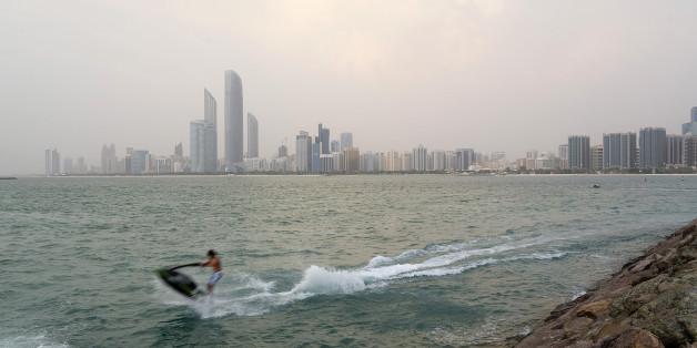 Skyscrapers stand on the city skyline beyond a jet skier passing close to the shore in Abu Dhabi, United Arab Emirates, on Monday, Aug. 12, 2013. As Dubai recovers from its slump caused by the global financial meltdown, Abu Dhabi is expanding faster, according to figures from their governments published last month and building projects and tourism mean the non-oil economy has overtaken Dubai's entire output, the data showed. Photographer: Duncan Chard/Bloomberg via Getty Images