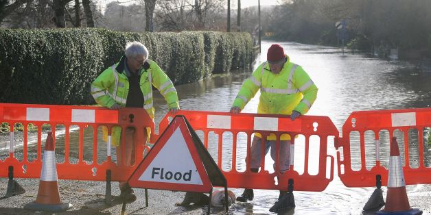Workers from the Worcestershire Highways Department place barriers in front of a flooded road in Fladbury, Worcestershire.