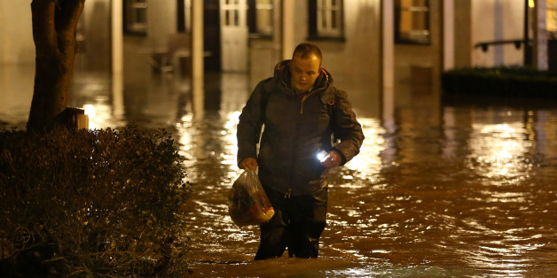 DORKING, UNITED KINGDOM - DECEMBER 24:  A man wades through rising floodwater from the River Mole outside the Burford Bridge Hotel on December 24, 2013 near Dorking, England. Christmas plans have been badly affected for thousands of people after storms across the UK have resulted in flooding, power cuts and significant problems with transport infrastructure.  (Photo by Peter Macdiarmid/Getty Images)