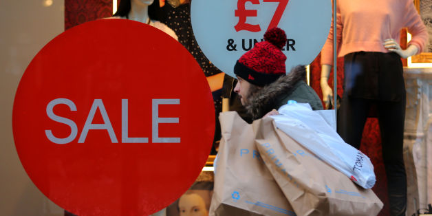 A shop on Market Street in Manchester advertises its sale, as shoppers buy last minute items before Christmas Day.