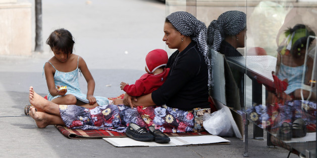 A Roma woman and her children begs place de la Bastille in Paris, on August 22, 2012. The French government seeks to end a row over its treatment of ethnic Roma migrants in a move that could result in Bulgarian and Romanian citizens being granted the right to work in France.  AFP PHOTO KENZO TRIBOUILLARD        (Photo credit should read KENZO TRIBOUILLARD/AFP/Getty Images)