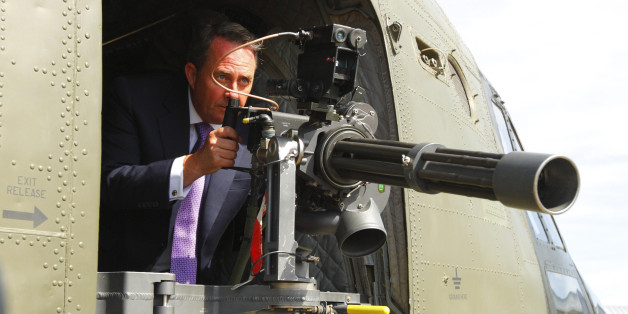Defence Secretary Dr Liam Fox looks through the sights of a machine gun aboard a Chinook helicopter at RAF Odiham.