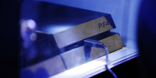 A logo sits above a USB cable attached to a PlayStation 4 (PS4) games console, manufactured by Sony Corp., during the Eurogamer Expo 2013 in London, U.K., on Saturday, Sept. 28, 2013. Last year, the number of consoles in consumers' homes, including the Xbox 360, PlayStation 3 and Wii U, stood at 238 million, according to IHS Screen Digest. Photographer: Matthew Lloyd/Bloomberg via Getty Images
