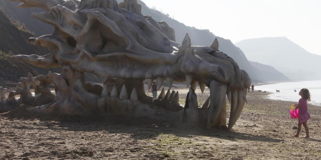 EDITORIAL USE ONLY Pantha Bradbury, three, stands in front of a 39 feet-wide dragon skull, which has been created to celebrate the launch of HBOÕs Game of Thrones Season 3 on the television and movie service, blinkbox, on Charmouth beach on the Jurassic coast in Lyme Regis, Dorset.