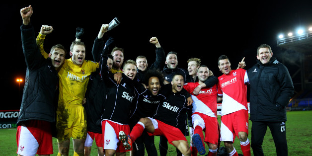 Kidderminster players and staff celebrate their defeat of Peterborough