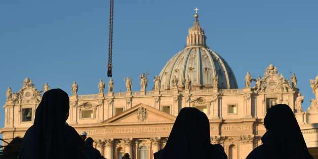 Nuns watch during the setup of the traditional Christmas tree on St Peter's square on December 5, 2013 at the Vatican. The tree, that was cut in Regensburg, Germany, is 25 metres tall, weights 7,2 tons and is 45-year-old.  AFP PHOTO / GABRIEL BOUYS        (Photo credit should read GABRIEL BOUYS/AFP/Getty Images)