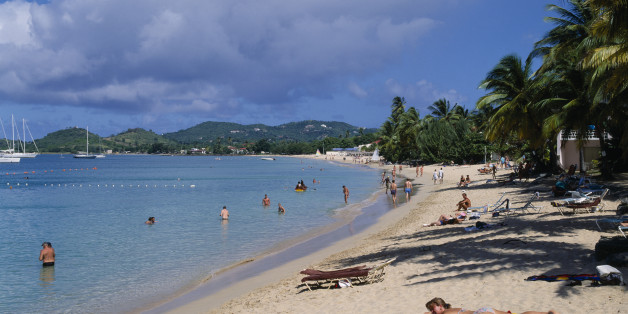 WEST INDIES St Lucia Reduit Beach Sunbathers and swimmers on sandy beach lined with palm trees. Yachts seen on the water and green hills behind