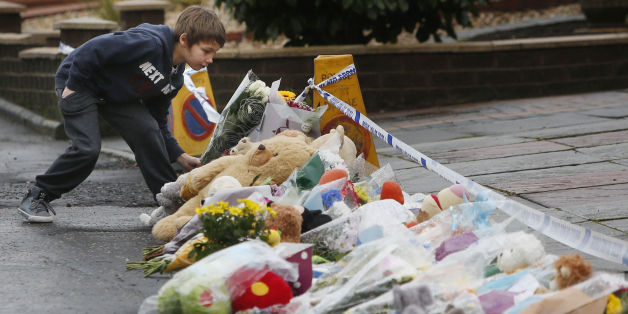 A young boy with floral tributes on Dunvegan Avenue in Kirkcaldy, Scotland: Danny Lawson/PA Wire