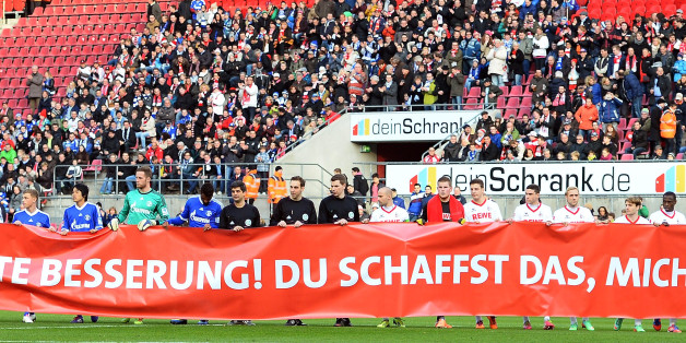 COLOGNE, GERMANY - JANUARY 18:  Players of Schalke and Koeln show a banner for Michael Schumacher prior to a test match between 1. FC Koeln and FC Schalke 04 at RheinEnergieStadion on January 18, 2014 in Cologne, Germany.  (Photo by Lars Baron/Bongarts/Getty Images)