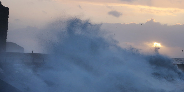 A man looks out from the beach at sunrise at West Bay during stormy weather on January 3, 2014 in Dorset, England.