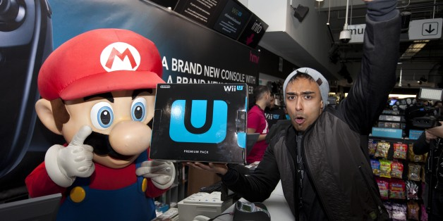 Izzy Rahman, 25, from London is the first to buy the Nintendo Wii U from the HMV store on London's Oxford Street, after queuing for six days for the launch.