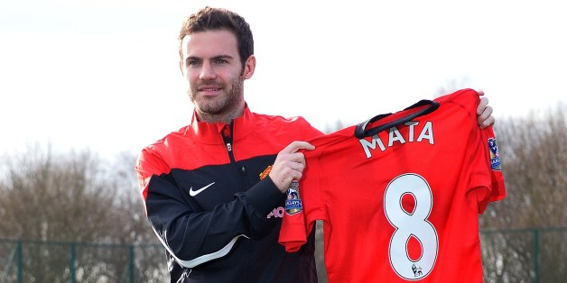 Manchester United's new signing, Spanish midfielder Juan Mata, poses with a team jersey at the club training ground in Manchester, north west England, on January 27, 2014. Manchester United manager David Moyes said on January 26 that the club-record acquisition of Spanish midfielder Juan Mata from Chelsea would be the first of many new signings this year. United completed a move for Mata on Saturday for a fee of 37.1 million GBP (61.2 million USD, 44.8 million euros), eclipsing the 30.75 million
