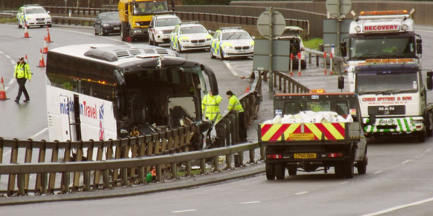 Emergency workers at the scene between junction 25 and 26 eastbound on the M4 in south Wales following a smash involving a lorry, bus and a number of cars at around 9.30am this morning.