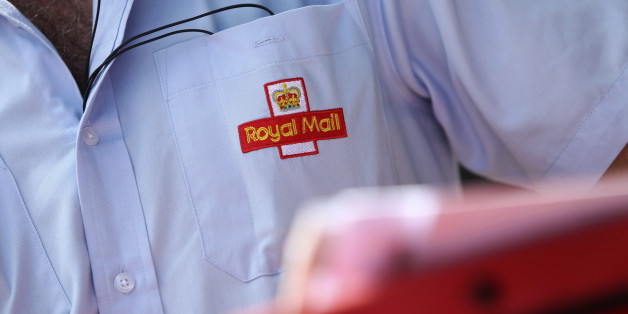 An embroidered logo sits on the shirt pocket of a Royal Mail Group Ltd. postman as he delivers mail in Hornchurch, U.K., on Wednesday, July 10, 2013. The U.K. government will sell a majority stake in Royal Mail Group Ltd., the 360-year-old state postal service, through an initial public offering before the end of March, Business Secretary Vince Cable said. Photographer: Chris Ratcliffe/Bloomberg via Getty Images