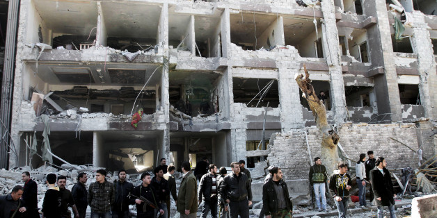 Syrian security officers gather in front the damaged building, attacked by al-Qaida-style group Jabhat al-Nusra, a shadowy group of veterans of jihad in Iraq, Libya and elsewhere