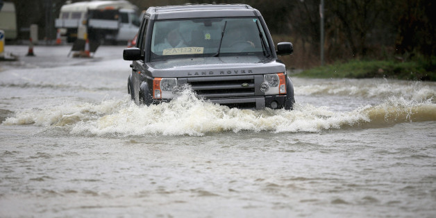 Residents drive through flood water on February 11, 2014 in Chertsey, United Kingdom.
