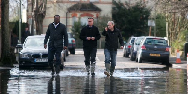 Prime Minister David Cameron meets with resident Ray Connerlley(right) and Kwasi Kwarteng, the MP for Spelthorne, on a flooded Guildford Street in Staines-upon-Thames.