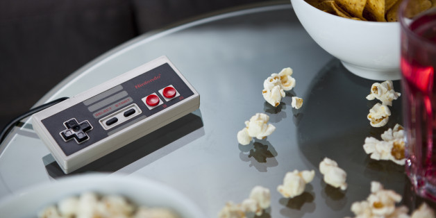 A vintage Nintendo NES controller photographed on a glass table, surrounded by bowls of snacks, taken on July 9, 2013. (Photo by Philip Sowels/Future Publishing via Getty Images)