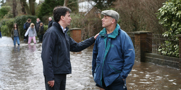 WRAYSBURY, ENGLAND - FEBRUARY 11:  Labour party leader Ed Miliband (L) talks with resident Peter Horner standing in floodwater on February 11, 2014 in Wraysbury, England. The Environment Agency has issued severe flood warnings for a number of areas on the river Thames west of London. Thousands of homes are under threat and may have been evacuated.  (Photo by Peter Macdiarmid/Getty Images)