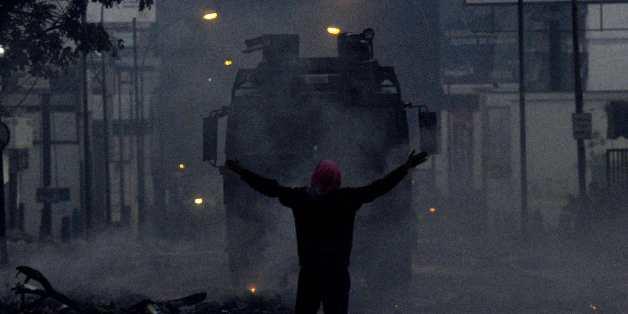 Un manifestant vénézuélien face à un char anti-émeute à Caracas