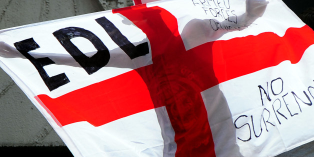 A man holds a flag during a EDL march at Centenary Square in Birmingham.