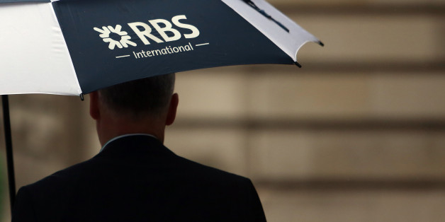 A pedestrian carries a Royal Bank of Scotland Group Plc (RBS) branded umbrella in London, U.K., on Friday, Nov. 1, 2013. Royal Bank of Scotland Group expects to post a 'substantial' full-year loss after transferring 38.3 billion pounds ($61 billion) of its worst loans to an internal bad bank under government pressure. Photographer: Chris Ratcliffe/Bloomberg via Getty Images