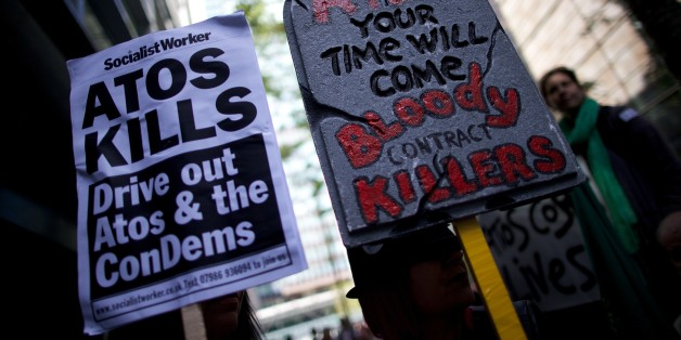Protesters carry placards during a protest against multinational IT firm and Paralympics sponsor Atos outside the company's head office in London on August 31, 2012. Protesters are outside Atos to protest there involvement in the tests on incapacity benefit claimants that has been awarded to them by the Department of Work and Pensions. Disabled and anti-cuts campaigners have been rallying as they claim the tests for people on disability by Atos are 'damaging and distressing'. AFP PHOTO / ANDREW