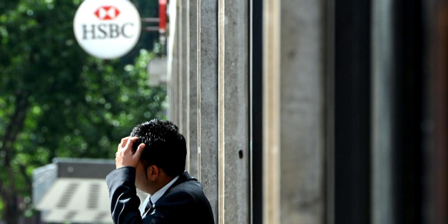 A member of staff outside a HSBC branch on Victoria Street, London as the banking giant today warned it will cut up to 30,000 posts by 2013 as the jobs cull among the world's big banks gathers pace.